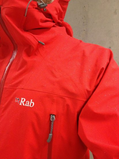 The Rab, showing sealed pockets, hood adjustments and some DWR action.